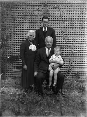 Family portrait in front of wooden garden trellis