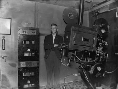 Cinema projector and projectionist in projection room; John McGuire; Illingworth (Firm); 1930s