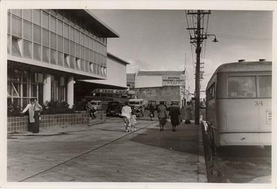 Photograph of a street with a bus outside a building on the left and several people