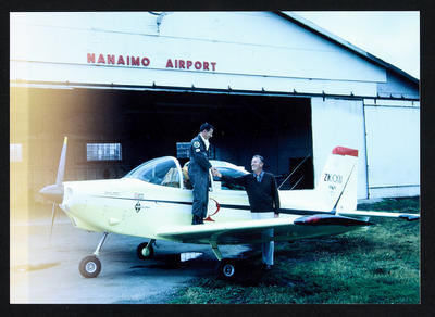 """[Cliff Tait standing on wing of Airtourer ZK-CXU """"Miss Jacy"""" at Nanaimo Airport, Canada]"""