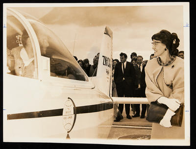 [Joyce Tait welcoming Cliff Tait on tarmac from his around the world trip]