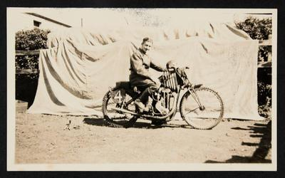 [Charlie Buchanan seated on motorcycle]