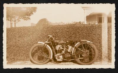 [Velocette motorcycle parked near hedge]