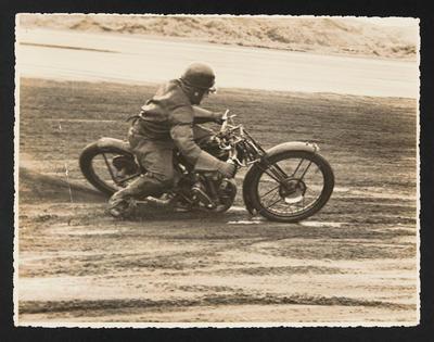 [Motorcyclist racing on Muriwai Beach]