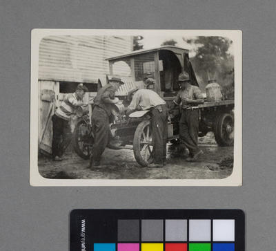 [Print of men fixing a flatbed truck]