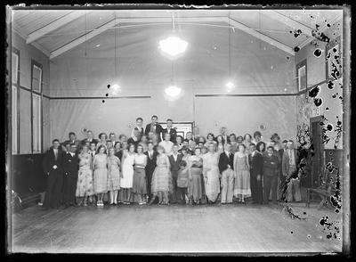 [Black and white glass plate negative group portrait inside a hall]