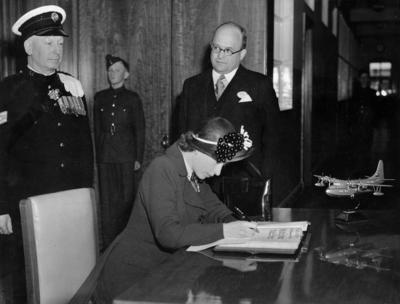 Photograph of Princess Elizabeth signing a book at Short Brothers and Harland's factory in Belfast