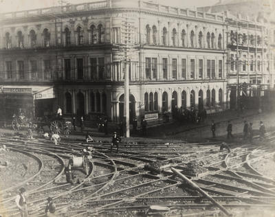 [Steel tram tracks being laid at the intersection of Queen and Custom Streets]
