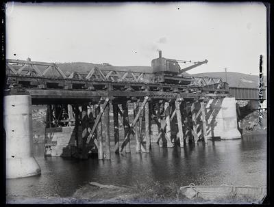 [Cranes in process of bridge construction over a river]