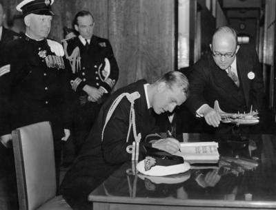 Photograph of Prince Philip signing a book at Short Brothers and Harland's factory in Belfast