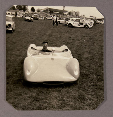 [Heron MK1 Sports Racing Car parked at race track field man seated in car]