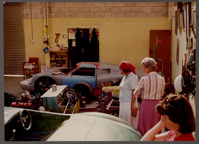[Heron MK4 GT 40 body in workshop with people in foreground]