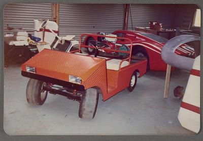 [Orange buggy in workshop]
