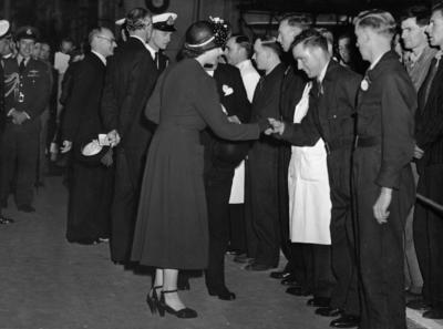 Photograph of Princess Elizabeth and Prince Philip talking to a group of male Short staff in a hangar