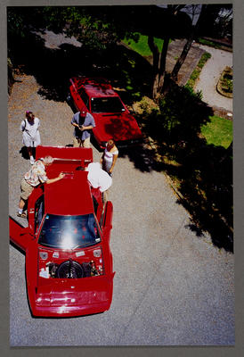 [Red Heron MJ1 with unidentified people on a suburban street, aerial view]