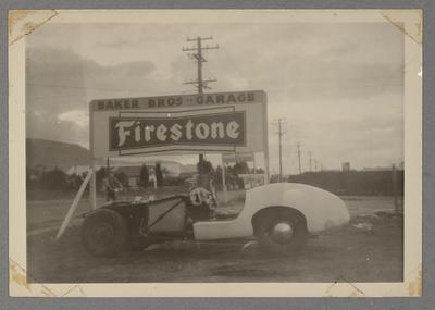 [Racing automobile beside Firestone sign]