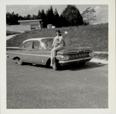 [Unidentified person and dog seated on automobile bonnet]