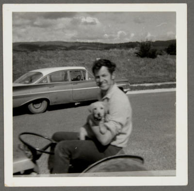 [Unidentified person and dog seated on lawnmower]