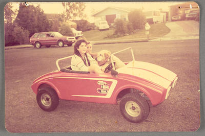 [Two unidentified people and a dog in a toy car]