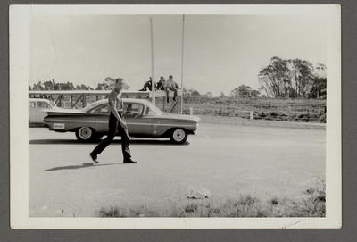 [Unidentified man walking past automobile]