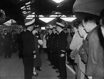 Photograph of Princess Elizabeth and Prince Philip talking to a group of Navy officers in a hangar