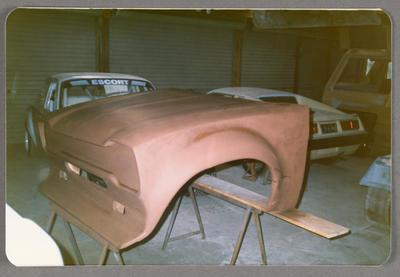 [Bonnet of automobile in refurbishment]