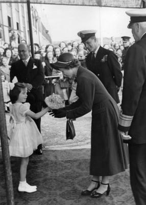 Photograph of Princess Elizabeth receiving a bunch of flowers from a small girl