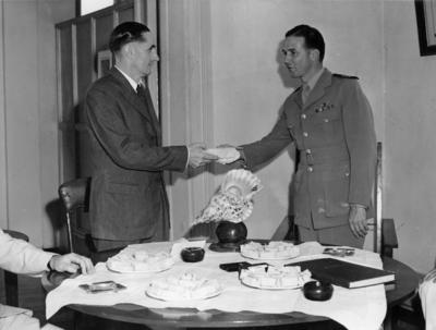 Photograph of the Deputy Mayor of Suva handing a package to Captain McGrane
