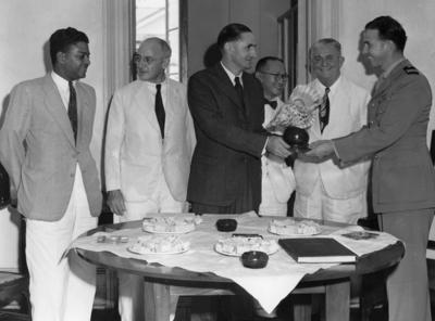 Photograph of the Deputy Mayor of Suva handing a shell lamp to Captain McGrane as several other men look on