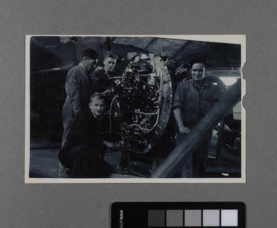 [John Cranwell and three other unidentified aviation fitters working on an engine]